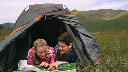 Happy couple reading map lying in their tent
