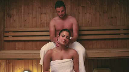 Man giving his girlfriend a neck massage in the sauna