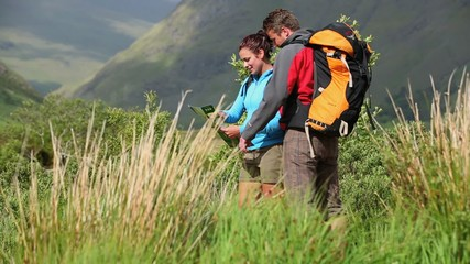 Active couple hiking together and reading map
