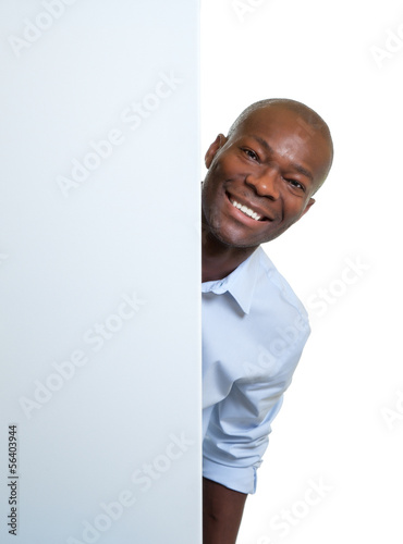 Laughing african businessman behind a signboard