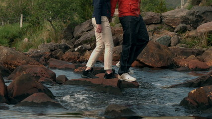 Couple crossing a stream together in the countryside