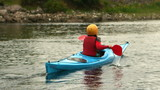 Woman kayaking in a river away from the camera