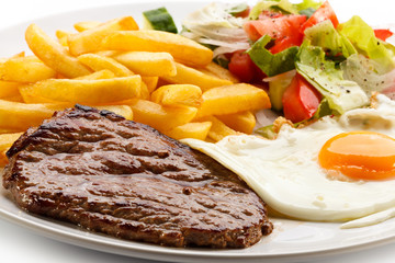 Grilled steaks, French fries, fried egg and vegetables