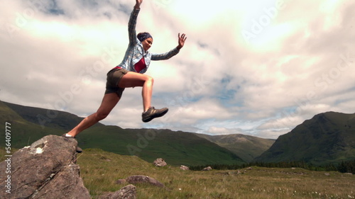 Athletic woman jumping off a rock in the countryside
