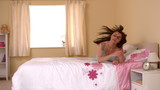 Cute young woman rolling on her bed