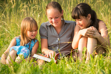 Children reading book on the park together
