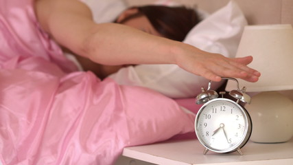 Irritated young woman throwing her ringing alarm clock