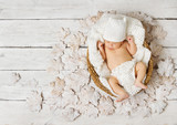 Newborn baby sleeping on white wooden leaves