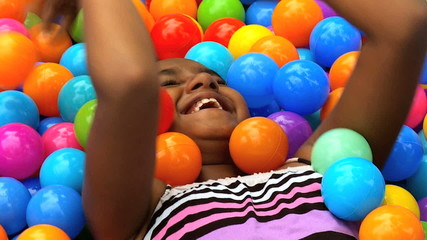 Close Up Laughing Young Ethnic Girl Playing Plastic Balls