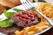 hamburger con ketchup e contorno di patate fritte