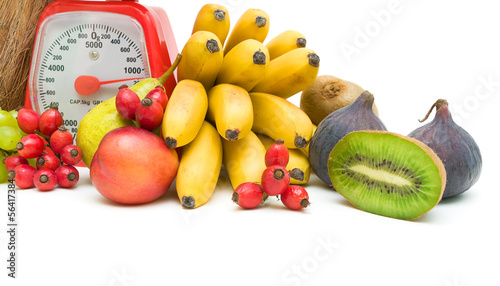 Fruit and kitchen scales on a white background