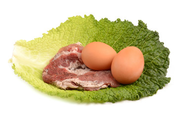 raw steak and eggs on a leaf of cabbage