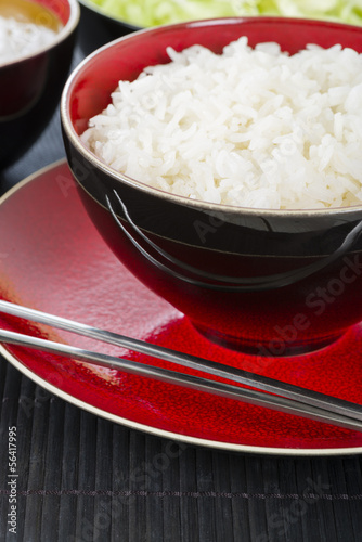 Boiled Rice - Steamed rice in a bowl with metal chopsticks.