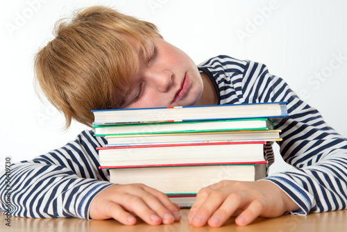 boy is sleeping on his books