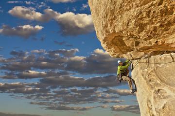 Climber struggles up a cliff.