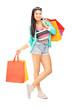 Attractive casual female posing with many shopping bags
