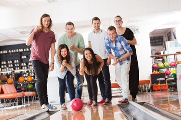 Woman Bowling While Friends Cheering in Club