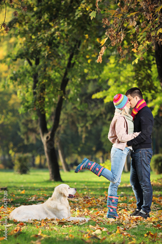 Male and female kissing in a park and a dog watching them