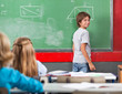 Little Boy Standing By Board In Classroom
