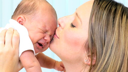 Loving Mother Kissing Baby Daughter