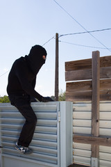 Thief jumping a fence