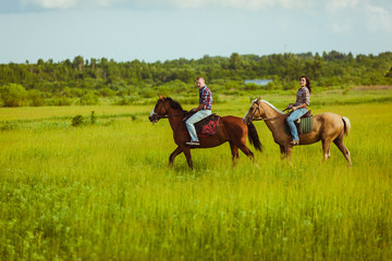 couple riding on horses across the field