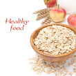Oat flakes in wooden bowl and apples in the background, isolated