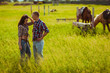 couple standing on farm with horses