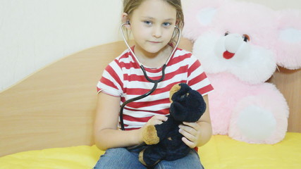 girl listens to a stethoscope stuffed dog, close-up