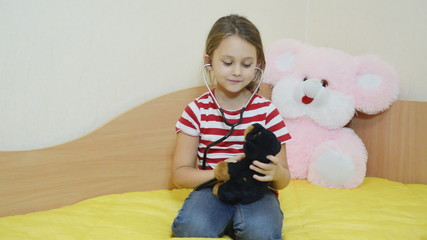 girl listens to a stethoscope stuffed dog