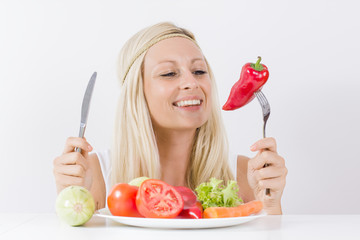 Happy woman eating vegetable