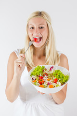 happy young woman eating fresh vegetable