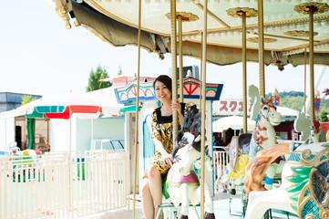 メリーゴーラウンドに乗っている女性