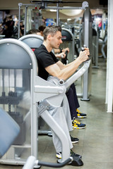 man exercising on machines