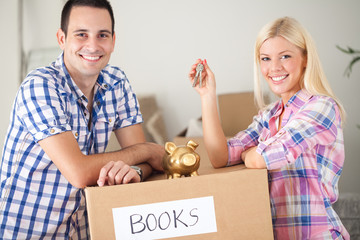 couple with piggy bank and keys with moving boxes