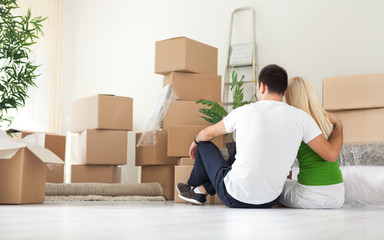 Couple sitting in room full of moving boxes