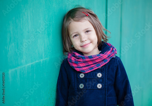 Portrait of preschooler girl near green wall