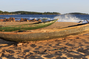 Dugout fishing canoe on the beach with coast and spray in the ba