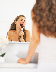 Happy young woman singing in makeup brush in bathroom