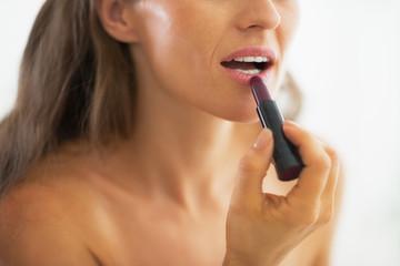 Closeup on woman applying lipstick in bathroom