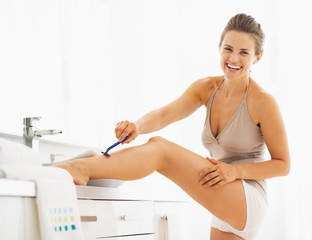 Smiling woman shaving legs in bathroom