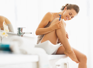 Happy woman checking legs after shaving