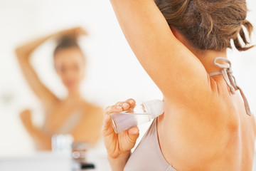 Closeup on woman applying roller deodorant on underarm