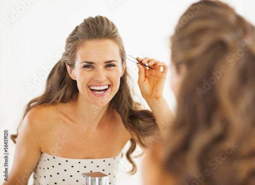 Happy young woman with tweezers in bathroom