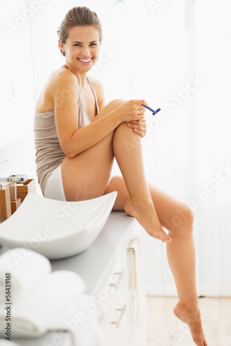 Happy woman shaving legs in bathroom