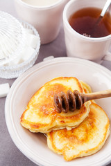 Pancakes with honey served for breakfast. Shallow DOF
