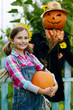 Autumn harvests, Scarecrow and happy girl
