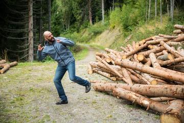 Mann flieht vor herabrollenden Baumstämmen