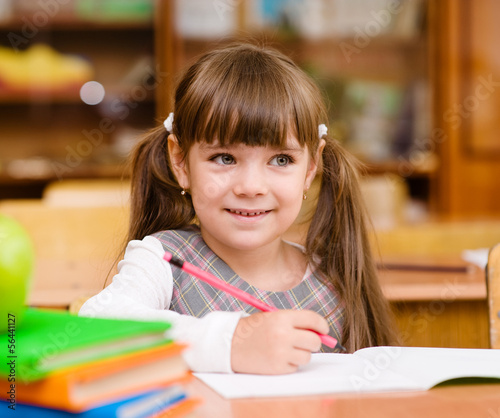 girl drawing in copybook in classroom