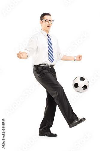 Handsome male with tie and shirt playing with a soccer ball